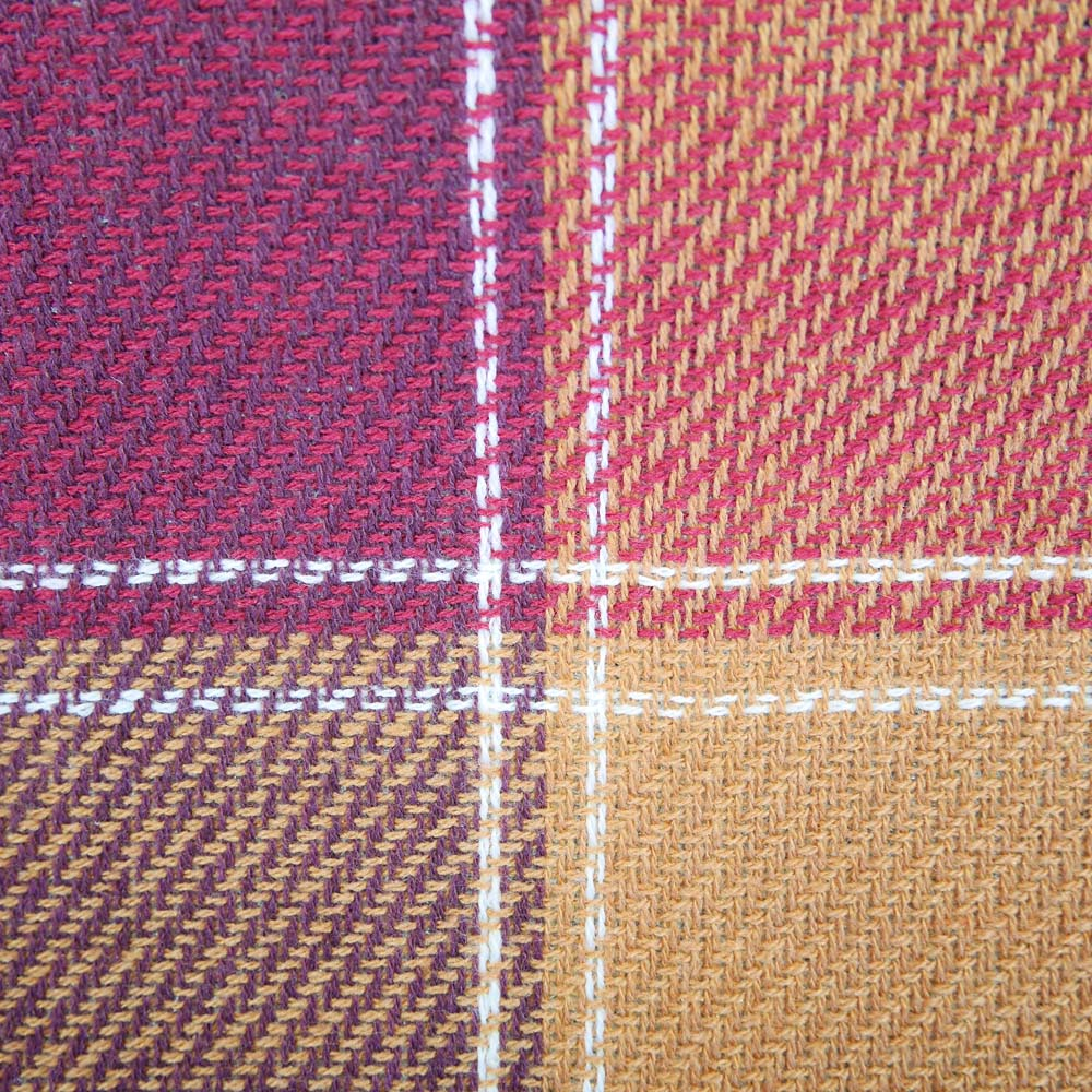 Close up of maroon and brown tartan picnic rug